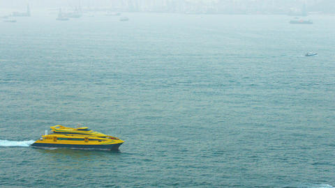 Bright yellow. luxury motor yacht. cruising through a bay off Hong Kong. China Live Action