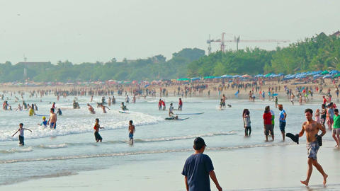 Crowd of people in water on popular balinese tourist attraction Kuta beach Live Action
