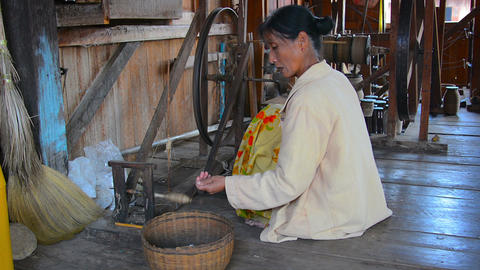 Woman spin yarn thread on traditional wooden distaff spinning wheel Live Action