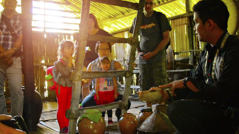 guide tell about the traditional malay production of rice wine to tourist group Footage