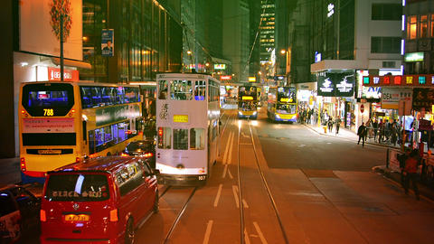 Double-decker trams and other transport traffic on night street in Hong Kong Footage