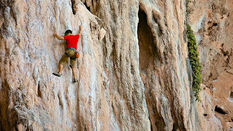 Rock climber climb up limestone cliff in safety belt on a rope Footage