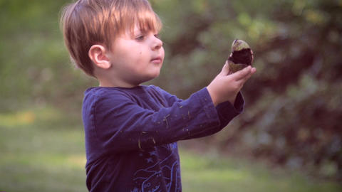 An innocent young child holding up something and asking what it is in slow motio Footage