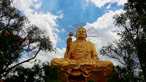 Golden Sitting Buddha Statue against Cloud Motion in Blue Sky Footage