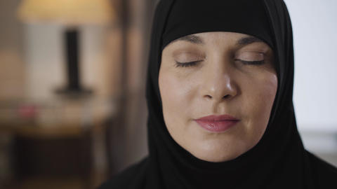 Close-up of beautiful young Muslim lady applying perfume. Attractive woman in Live Action