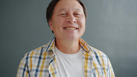 Happy Asian man smiling feeling cheerful and carefree om gray background Live Action