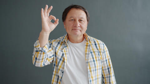 Mature Asian man showing OK hand gesture smiling looking at camera alone Live Action
