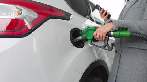 Woman using smartphone while her car is refueling. Slow motion Live Action