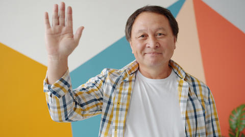 Cheerful Asian man waving hand smiling standing indoors at home alone Live Action