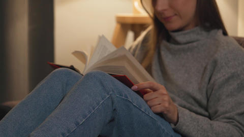 Woman lying on the couch in a cozy room and reading book in the evening Live Action