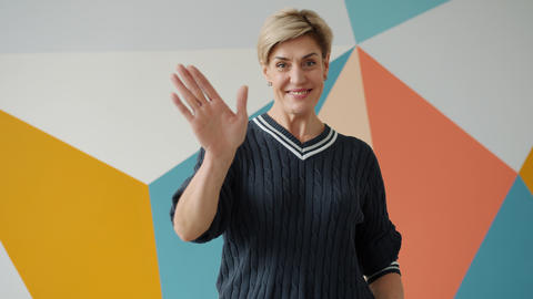 Friendly adult woman with short blond hair waving hand making hello gesture at Live Action