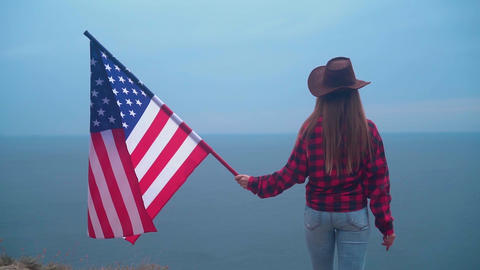 Girl in a cowboy hat with an American flag. America symbol Live Action