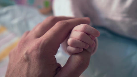 Hand of an adult male holding a small baby hand. The concept is the care and Live Action