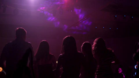 Group of silhouetted people dancing in a dark banquet hall for a wedding Live Action