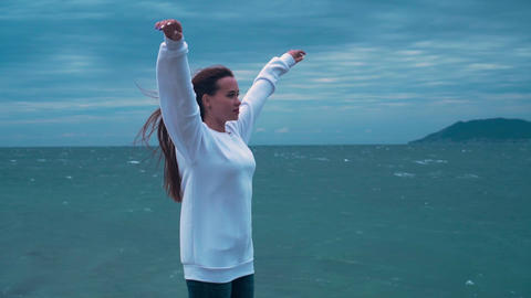 A girl stands on the seashore in a storm. Cloudy day, the sea in a storm, a girl Live Action