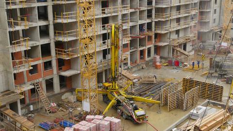 Concrete pump truck at a construction site lifts the boom Live Action