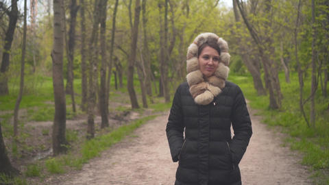A girl in a warm black jacket walks through the woods. The girl follows the Live Action