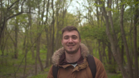 A man in a warm broun jacket walks through the woods. The man goes in front, the Live Action