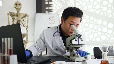 Attractive contented young asian medical worker looking under microscope in the Live Action