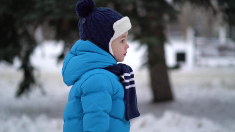 Cute four years old boy in blue winter clothes walks in snowy street Live Action