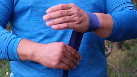 Overweight adult man in blue sportswear rewinds his hand with a blue textile bandage for sports and Acción en vivo