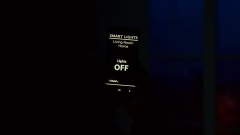 Close up of man hand holding a voice activation smart light app for tuning on Live Action