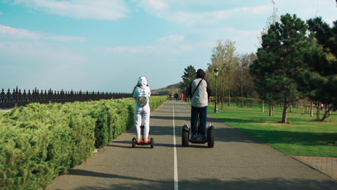 Young couple moving on segway in park. Active tourists getting segway tour Live Action