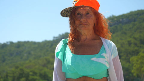 Youthful old woman in blue bikini walking by the sea Live Action