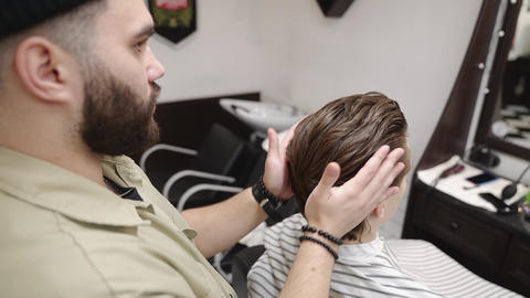 The client receives a haircut and hair styling in a beauty salon Live Action