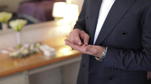 Handsome groom holds wedding rings in his hand. Wedding morning. Businessman Live Action