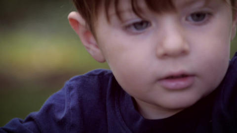 Slow motion of a cute little boy intensely focusing on his toys while playing ou Footage