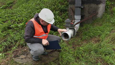 Engineer with documentation near the dirty pipe Footage