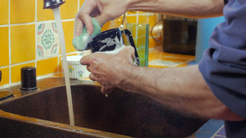 A man washing a cup with a sponge with a fast shutter speed - dolly Footage