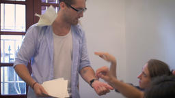 A young man loses control of a meeting while his coworkers throw paper at him. H Footage