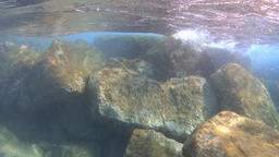 Waves splashing under water over the rocks, real time Footage