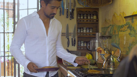 An attractive young hispanic man cooks breakfast for his wife / girlfriend in a  Footage