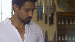 Medium dolly shot of an attractive young latino man in his 30's cooking breakfas