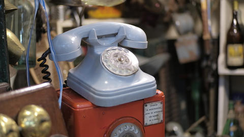 Dolly left shot of a blue vintage rotary dial telephone for sale on a flea store Live Action