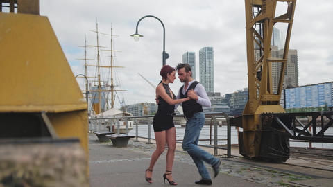 Two proffesional tango partners doing zigzag dance steps in Puerto Madero Live Action