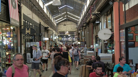 The main hall of San Telmo Fair full of tourists shopping antiques. DOLLY IN Live Action
