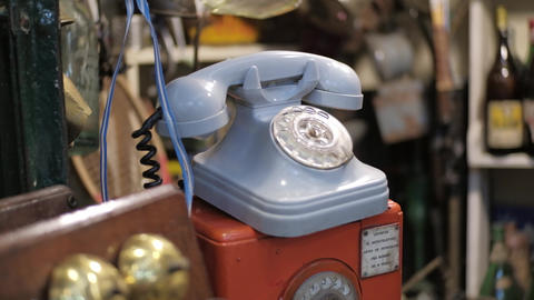Dolly right shot of blue vintage rotary dial telephone for sale on a flea store Live Action