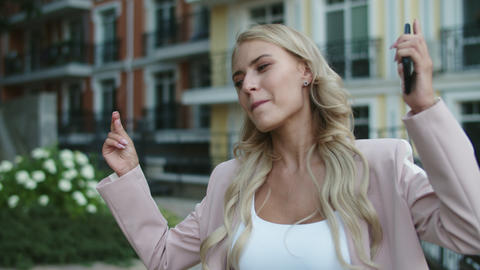 Portrait excited businesswoman dancing with phone in hand outside Live Action