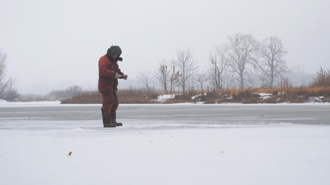 A fisherman on the ice of a frozen river catches fish Live Action