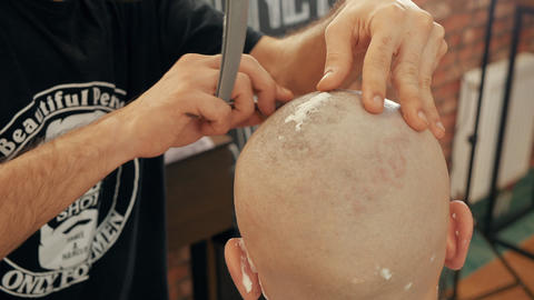 Male stylist shaving head of bald man with straight razor and foam in barber Live Action