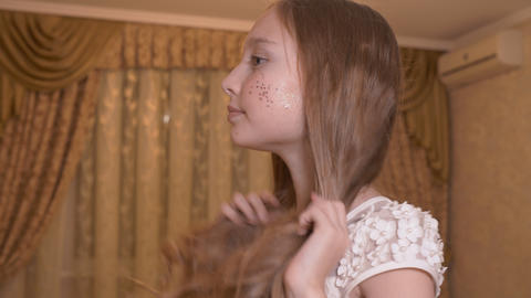 Portrait young girl with shining makeup face touching curly hair on bedroom Live Action