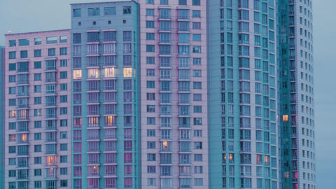 Timelapse of living apartment building windows at dusk to night - facade view Live Action
