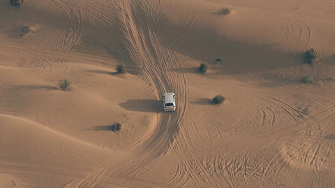 Aerial tracking shot of an unknown white SUV driving fast along sand dunes in Live Action