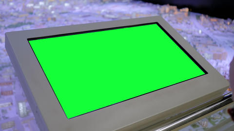 Woman looking at blank green display kiosk at exhibition - green screen concept Live Action