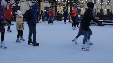 people, adults and children skating on the rink Live Action