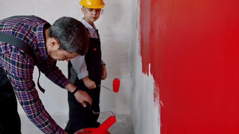 Apartment renovation - father and son covering roller in red paint Live Action